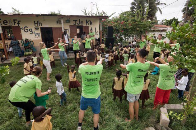 Otroci s prostovoljci v Gambiji stojijo v krogu na travniku. Imajo športni dan