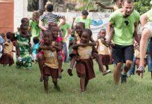 Otroci s prostovoljci v Gambiji, ki tečejo na travniku. Imajo športni dan