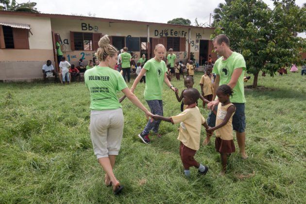 Otroci s prostovoljci v Gambiji na travniku