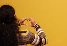 dekle pred rumenim zidom, ki z dlanmi ustvarja obliko srčka